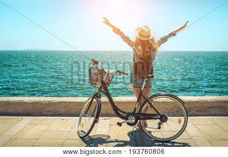 Blonde woman in summer hat with her bicycle walking coastline by the sea beach. Sea view. Freedom. Wind. Summer. Beach. Vacation. Looking to a sky and sea. Looking forward.