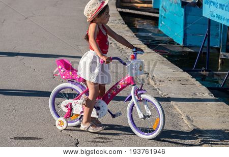 Undefined Surprised Little Girl On Bicycle At Annecy Lake. Haute-savoie, France