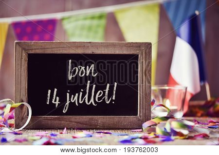 chalkboard with the text bon 14 juillet, happy 14 July, the National Day of France, written in French and a flag of France, on a wooden surface sprinkled with confetti and a garland in the background