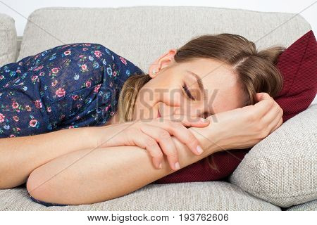 Picture of a beautiful young girl lying on the couch taking a nap at home