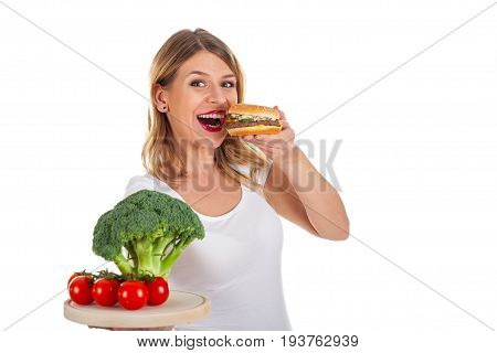 Picture of an attractive young woman holding a delicious hamburger and fresh vegetables on the other hand