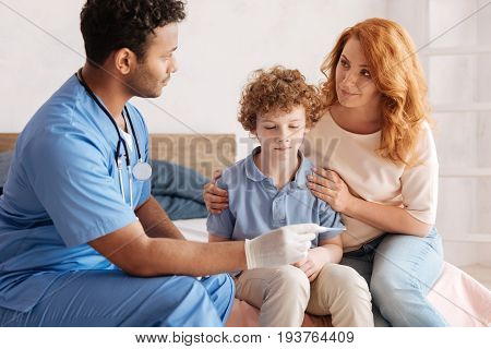 Have temperature. Upset man-child pressing his lips and looking downwards while sitting between mother and medical worker