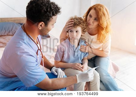 What should we do. Sick boy pressing lips and looking at doctor while keeping hands together