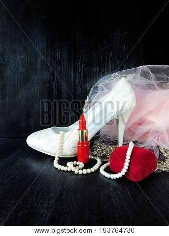 White stylish high heel shoe, pearl jewellery and red lipstick for a special occasion on a dark background. Empty place for a text