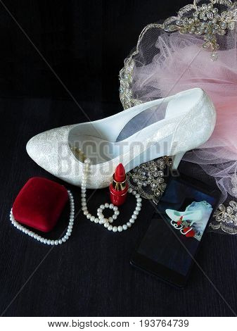 White female shoe with high heels, red lipstick and smartphone with the photo in the screen