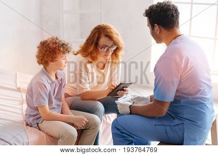 Wait a second. Attentive boy sitting near his mother, holding hands together while listening important information