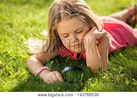 Girl nature young magnifying glass exploring lawn curiosity