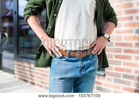 cropped shot of man in casual clothing standing with hands on hips on street