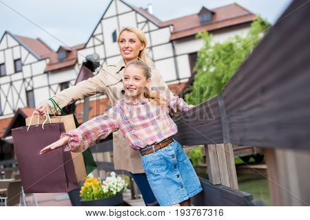 happy mother and daughter with shopping bags standing with arms outstretched near fence on street