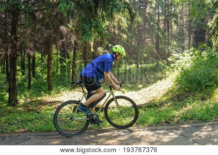 Cyclist with green helmet on a mountain road in forest. Black bicycle