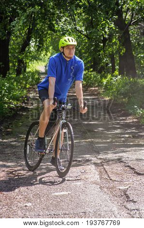 Cyclist with green helmet and blue t-shirt on a mountain road in forest. Black bicycle