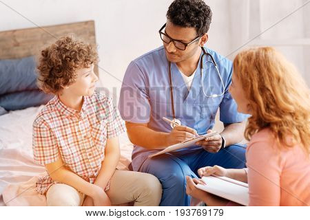 Listening you. Serious doctor wearing stylish glasses and keeping folder in left hand while making notes