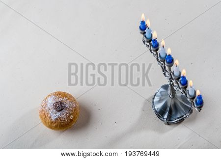 Hanukkah menorah candle holder for nine candles and sufganiyah - traditional deep-fried donut for Jewish holiday of Hanukkah