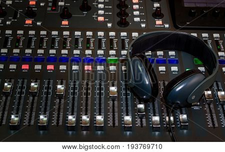 The audio equipment control panel of digital studio mixer and headphones close-up.