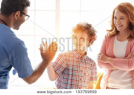Say goodbye. Positive delighted mother standing on the background and keeping smile on her face while looking at family doctor