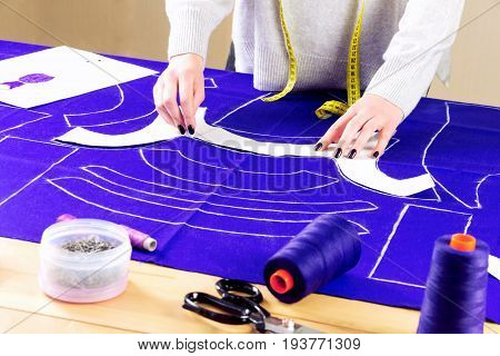 Workplace of a dressmaker: scissors pattern needles textile sewing spools and measure tape. Girl drawing a pattern for the dress.
