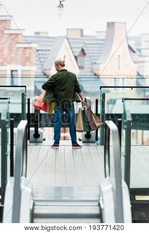 Back View Of Man Holding Multicolord Paper Bags While Standing On Escalator In Shopping Mall