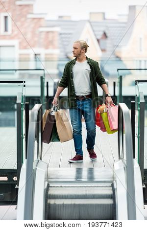 Handsome Young Man Holding Shopping Bags While Standing On Escalator And Looking Away