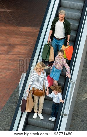 High Angle View Of Happy Young Family Holding Shopping Bags While Standing On Escalator