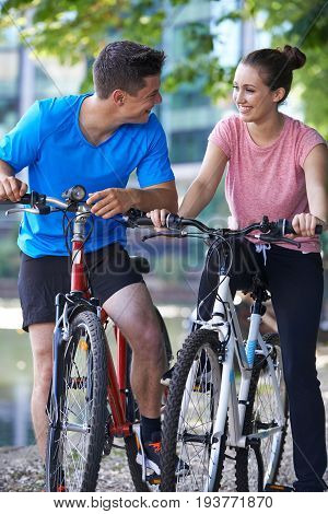 Young Couple Cycling Next To River In Urban Setting