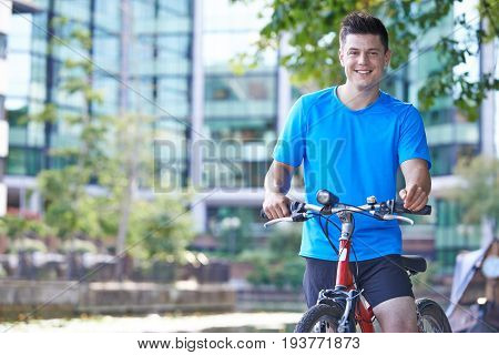 Portrait Of Young Man Cycling Next To River In Urban Setting