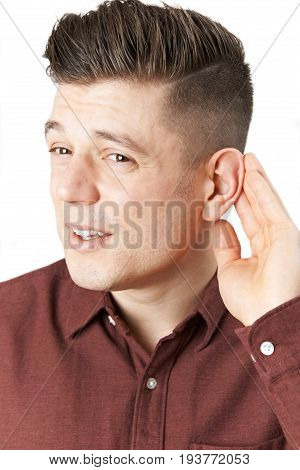 Studio Shot Of Young Man Suffering With Hearing Difficulties