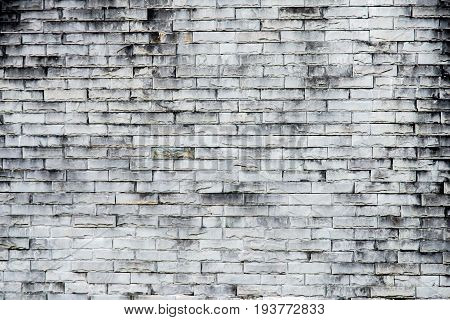 old gray brick wall texture background.Rough brick wall.Background of old vintage dirty brick wall with peeling plaster texture