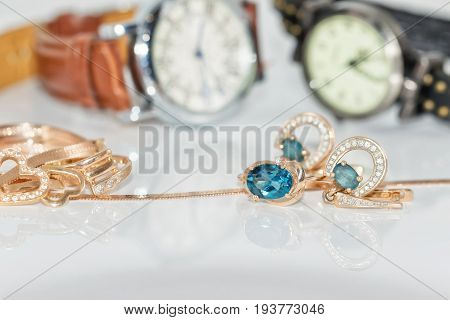 Gold Earrings With Topaz On Background Of Elegant Women's Watches