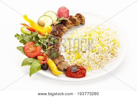 Grilled lamb kebab koobideh or kubide with rice and herb served on plain plate. Persian traditional cuisine and fusion food concept. Closeup studio shot from high angle view. Clean white background.