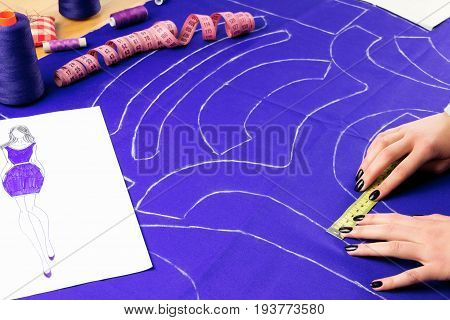 Workplace of a dressmaker: scissors pattern needles textile sewing spools and measure tape. Girl measuring patterns with the ruler