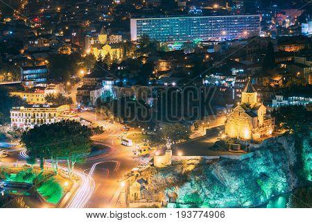 Tbilisi, Georgia - October 21, 2016: Night Evening Illuminated View Of Metekhi Church And Equestrian Statue Of King Vakhtang Gorgasali On Metekhi Cliff In Old Historic District Abanotubani. Night Traffic On Europe Square