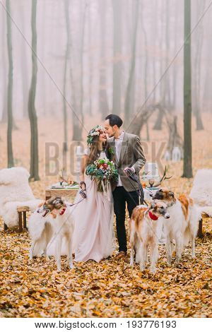 Cheerful newlywed couple is spending time with collis in the beautififul autumn park