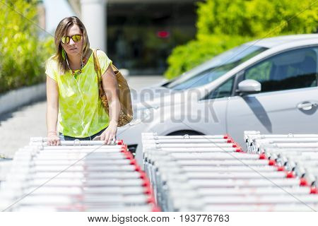 Young Confident Caucasian Happy Woman In A Big City Modern District With Smart Phone, Earphones, Con