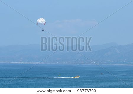 Parachuting Over A Sea, Towing By A Boat. Riding On A Parachute Behind A Boat. Travel Concep
