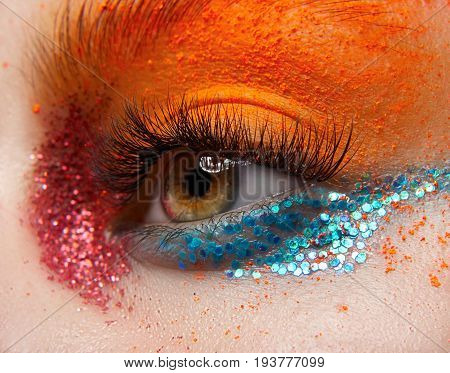 Macro And Close-up Creative Make-up Theme: Beautiful Female Eye With Red And Blue Sparkles And Orang
