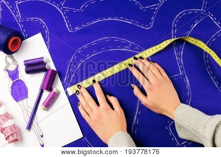 Workplace of a dressmaker: scissors pattern needles textile sewing spools and measure tape. Girl measuring patterns with the measuring tape