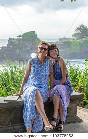 BALI, INDONESIA - MAY 4, 2017: Two woman on a background of Pura Tanah lot temple, Bali island.