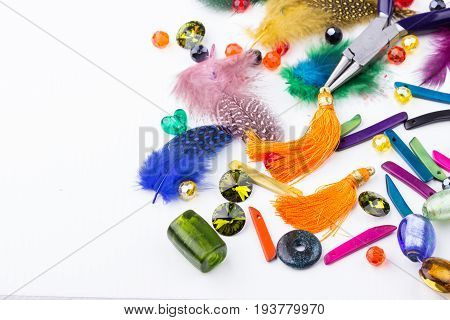 Jewelry making and beading components beads feather and tassel earings on white background. Selective focus.