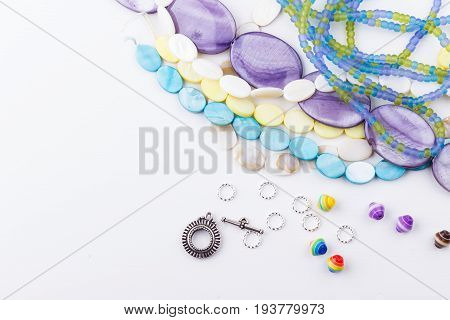 Glass and seed beads gemstone beads findings on white background. Selective focus.