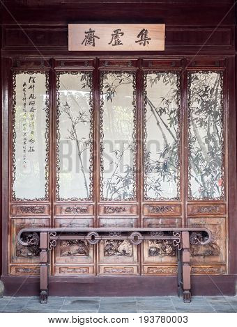 Suzhou, China - Nov 5, 2016: Master of Nets Garden (Wang Shi Yuan) - Ornate partition at entrance to a residence designed in the classical Chinese style, complete with long artistically crafted wooden desk.