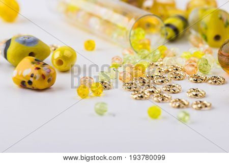 Yellow and lime glass and seed bead mix closeup on white background. Selective focus. Top view.