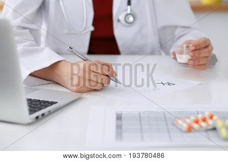 Female medicine doctor fills up prescription form to patient closeup. Panacea and life save, prescribe treatment, legal drug store, contraception concept.