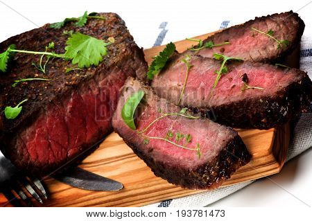 Sliced Delicious Roast Beef Medium Rare on Wooden Cutting Board Fork and Table Knife closeup