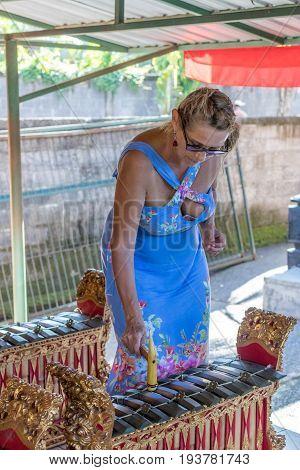 Woman playing on Traditional Balinese music instrument gamelan. Bali island.