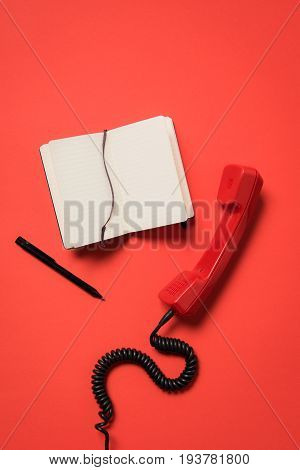 Close-up View Of Vintage Telephone Handset And Blank Open Notebook With Pen Isolated On Red