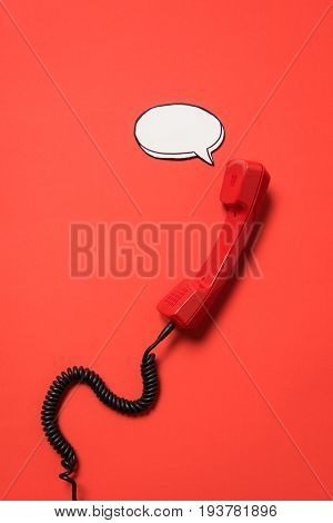 Close-up View Of Telephone Handset And Blank Speech Bubble Isolated On Red