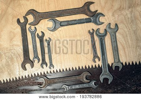 Rectangular Frame Of Old Rusty Wrenches And Saw On A Wooden Background, Diagonal Composition, With C