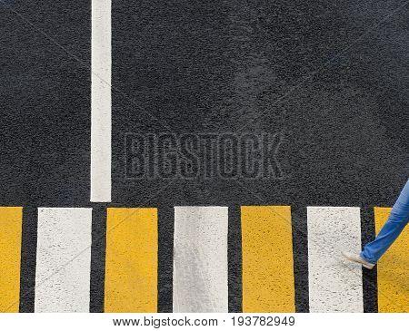 A pedestrian crosses the road on zebra crosswalk