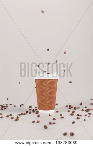 Disposable Coffee Cup With Falling Coffee Grains Isolated On Beige With Copy Space
