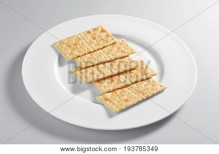 Plate with salty crackers isolated on grey background